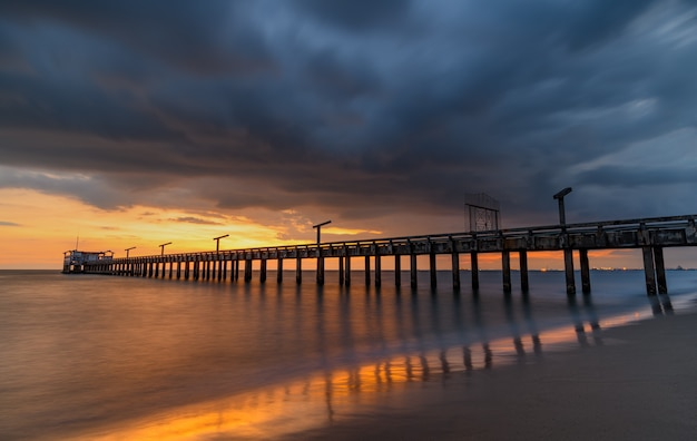 Длинный морской мост во время заката с теплым низким освещением и темной облачной тенью