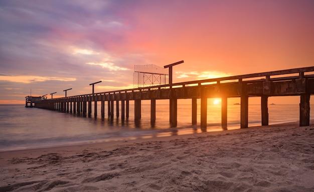 Длинный морской мост во время заката с теплым приглушенным освещением и темной тенью