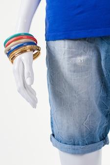 긴 반바지와 화려한 팔찌. 밝은 팔찌가 달린 마네킹 손. 여성을 위한 캐주얼 액세서리 세트. 보석류의 계절 판매.