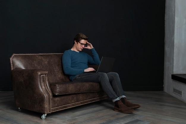 Uomo di angolo della ripresa frontale che osserva sul suo computer portatile