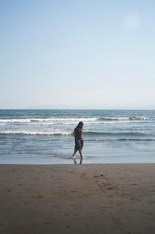 Colpo lungo donna asiatica in spiaggia
