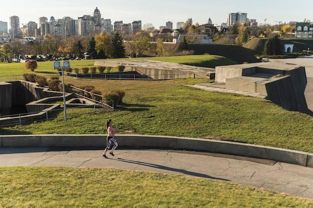 Long shot athlete jogging in the park
