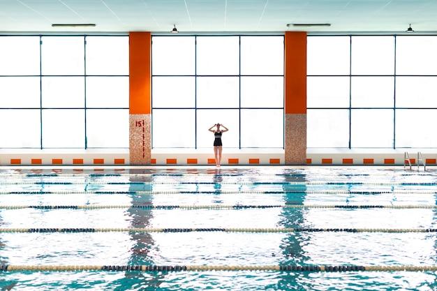 Спортсмен с длинным выстрелом, стоящий у бассейна