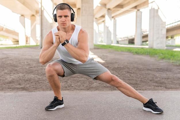 Long shot athletic man stretching