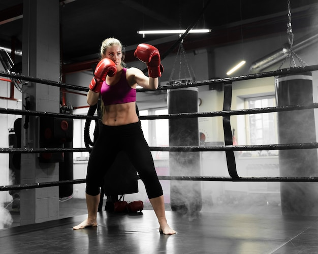 Long shot athletic woman training for a boxing competition