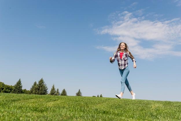 Long shot blonde girl running on grass