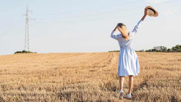Длинный выстрел блондинка женщина, наслаждаясь природой в поле с копией пространства