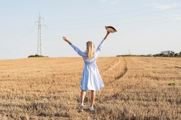 Длинный выстрел блондинка женщина, наслаждаясь природой в поле