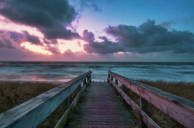 Long shot of a boardwalk leading to a beach with a colorful sunset in wenningstedt, sylt, germany