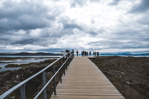 Long shot of a boardwalk with railing and tourists, overlooking a lake on a cloudy day