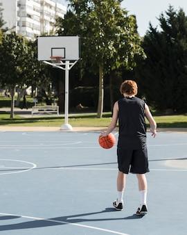 Colpo lungo del ragazzo che gioca a basket