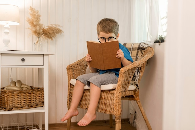 Long shot boy reading in an armchair