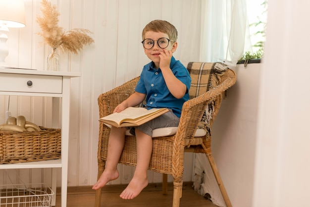 Long shot boy reading while sitting in an armchair
