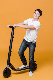 Long shot of boy with scooter