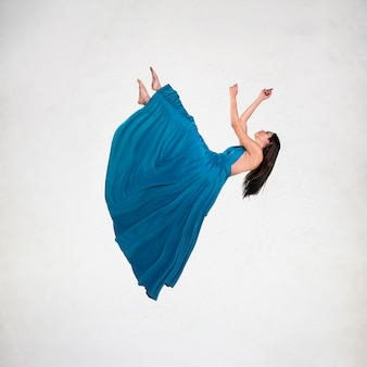 Long shot brunette woman in dress levitating