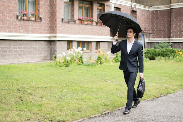 Long shot of businessman holding umbrella