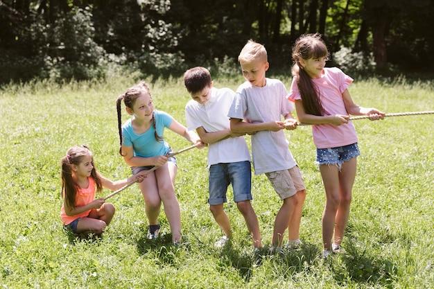 Long shot children playing tug of war