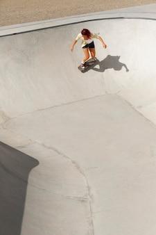 スケートボードで楽しんでいるロングショットのクールな女性