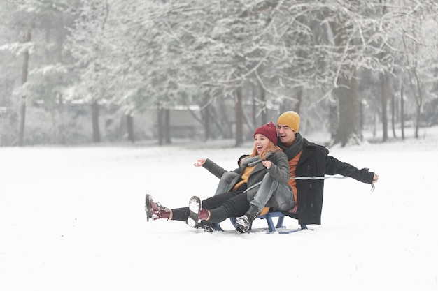 Long shot of couple being happy and sitting on the sleigh