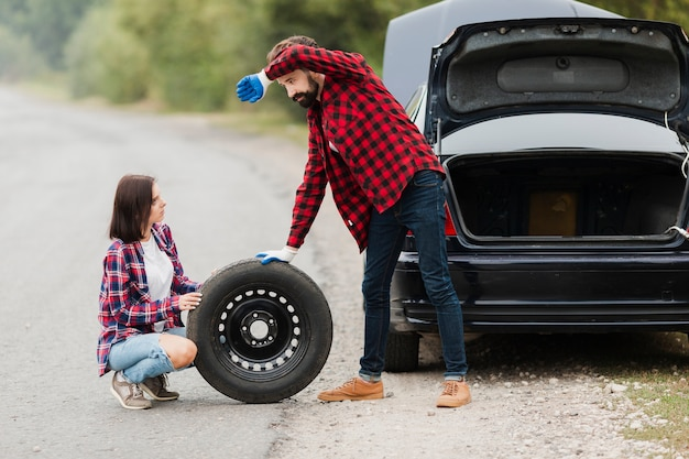 Long shot of couple changing tire