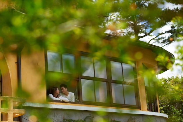 Long shot of couple cuddling on the terrace of a mansion