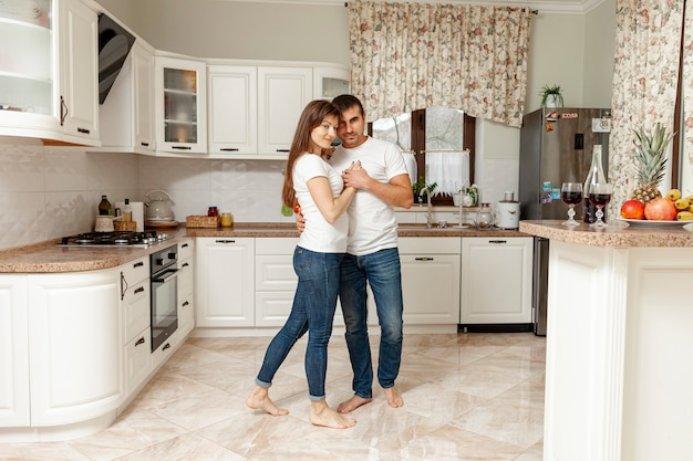 Long shot couple dancing in kitchen