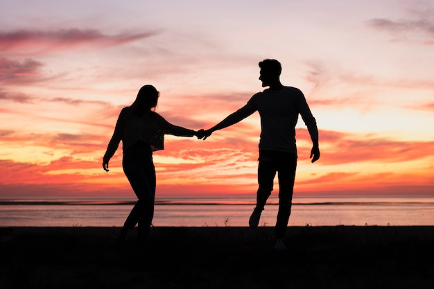 Long shot of couple holding hands at sundown