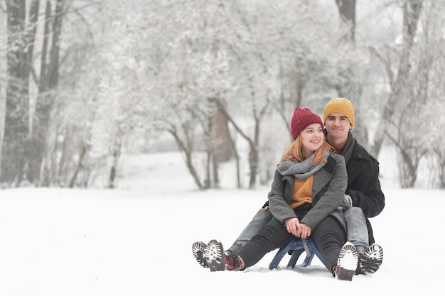 Long shot of couple sitting on sleigh front view