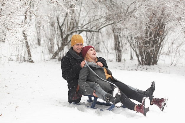 Long shot of couple sitting on a sleigh in the snow