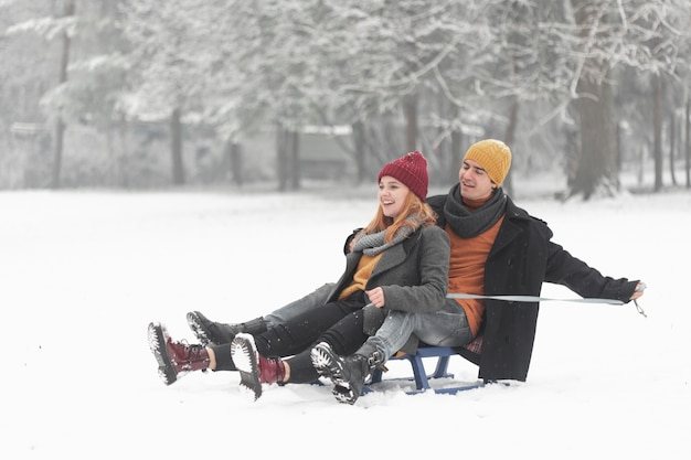 Long shot of couple sitting on sleigh in winter