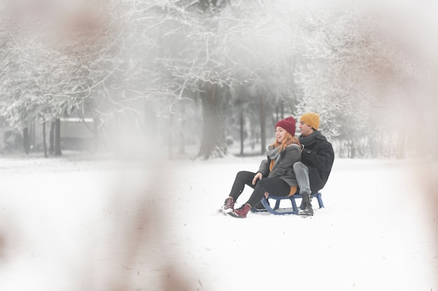Long shot of couple sitting on sleigh