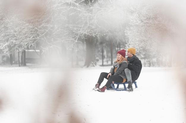 Long shot of couple sitting on sleigh