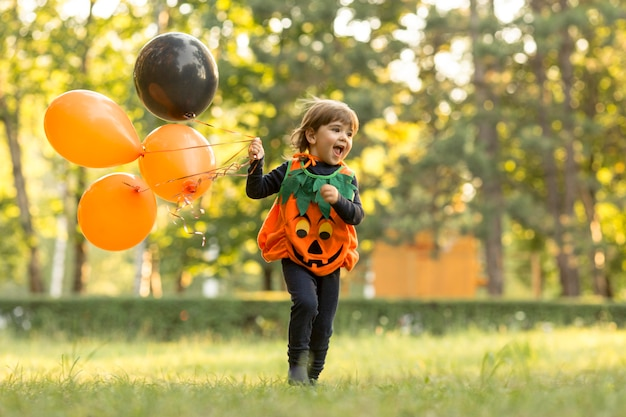 Long shot of cute little boy in pumpkin costume