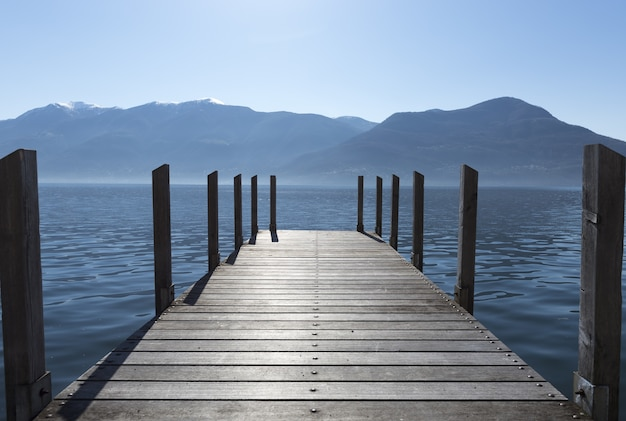 Long shot of the docks stretching out to the lake with mountains in the horizon