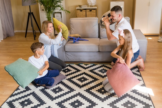 Long shot family playing with pillows