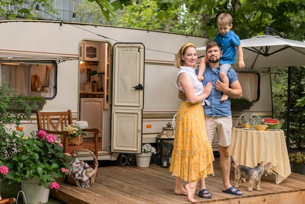 Long shot family posing next to their caravan