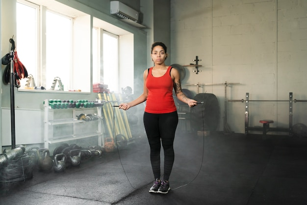Long shot female boxer training with a jumping rope