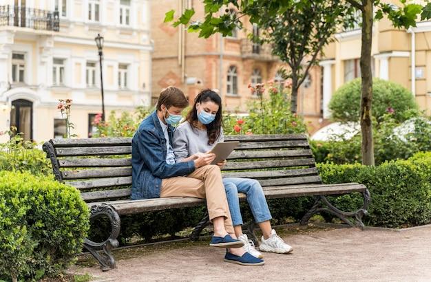 Друзья с длинными выстрелами смотрят на планшет в медицинских масках