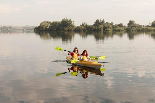 Long shot friends rowing in kayak