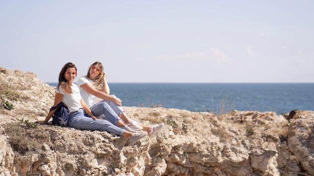 Друзья с длинным выстрелом сидят на камнях у океана с копией пространства