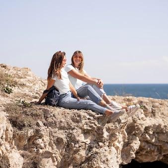 海の隣の岩の上に座っているロングショットの友達