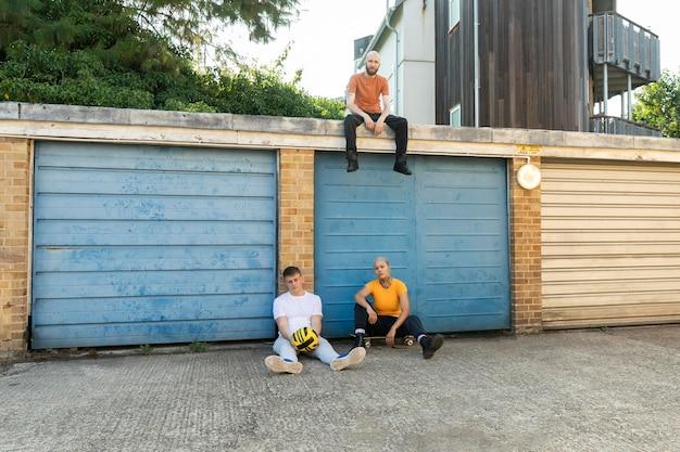 屋外に座っているロングショットの友達