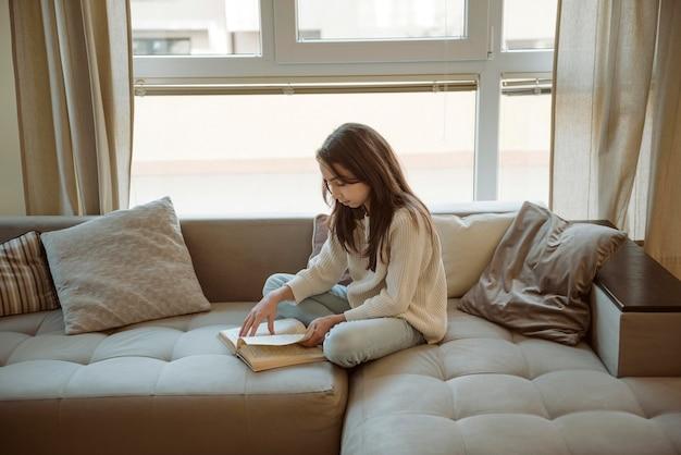 Длинношерстная девушка читает дома, находясь на карантине