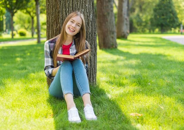 Long shot girl reading outside