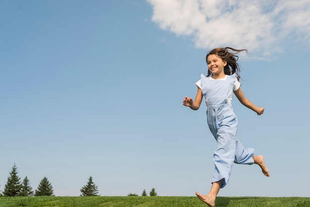 Long shot girl running barefoot on grass