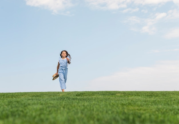 Long shot girl with long hair running on grass