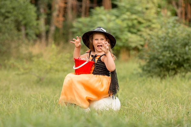 Long shot of girl with witch halloween costume in nature