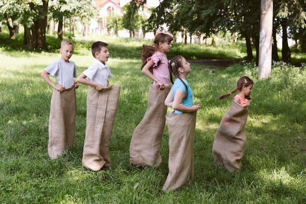 Long shot girls and boys running in burlap bags