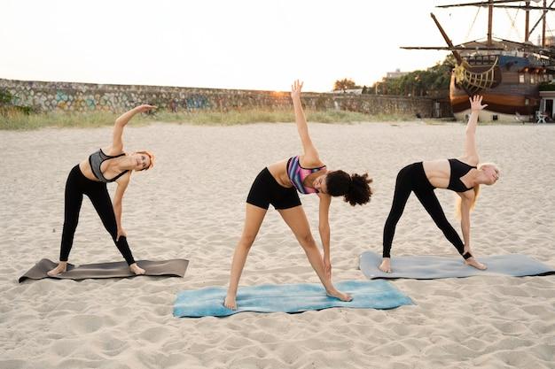 Campo lungo di ragazze che esercitano sulla spiaggia
