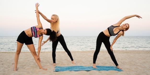 Long shot of girls exercising on beach